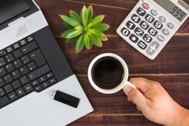 Photo of a laptop computer, cup of coffee, plant and calculator on a desk.